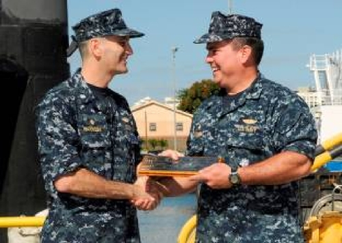 "USS Los Angeles (SSN 688) Commanding Officer Cmdr. Steven Harrison (left) passes on the ""Dick O'Kane cribbage board"" to USS Bremerton (SSN 698) Commanding Officer Cmdr. Howard Warner during a departure ceremony held at the Naval Station Pearl Harbor submarine pier.  The guardianship of the cribbage board is traditionally held by the oldest submarine in the Pacific Fleet. Los Angeles departed Naval Station Pearl Harbor Jan. 14, for her final voyage to Puget Sound Naval Shipyard for inactivation."
