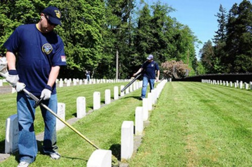 Senior Chief Intelligence Specialist Jason Wohlfehrt, left, and Senior Chief Aviation Ordnanceman Clayton Duncan, USS Ronald Reagan (CVN 76), remove overgrown grass around tombstones at the Washington State Veterans Home Cemetery during a community service project.