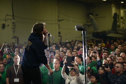 """U.S. 5TH FLEET AREA OF RESPONSIBILITY (Jan. 11, 2013) Adam Lazzara, lead vocalist for the band """"Taking Back Sunday,"""" performs for the crew of the aircraft carrier USS John C. Stennis (CVN 74) in the ship's hangar bay for a Navy Entertainment-sponsored visit to the ship."""