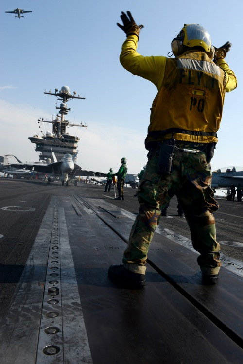 U.S. 5TH FLEET AREA OF RESPONSIBILITY (Jan. 20, 2013) Aviation Boatswain's Mate (Handling) 2nd Class Jesus Acosta directs an F/A-18E Super Hornet from the Tophatters of Strike Fighter Squadron (VFA) 14 aboard the aircraft carrier USS John C. Stennis (CVN 74).