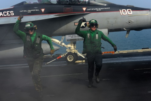 U.S. 5TH FLEET AREA OF RESPONSIBILITY (Jan. 28, 2013) Aviation Boatswain's Mate (Equipment) 3rd Class Charles Baldwin and Aviation Boatswain's Mate (Equipment) 3rd Class Mitchell Bode clear the launching area for an F/A-18F Super Hornet aboard the aircraft carrier USS John C. Stennis (CVN 74).