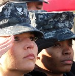 Allie Brazas salutes the flag during a ceremony for the hanging of a gold star banner in honor of her late husband.