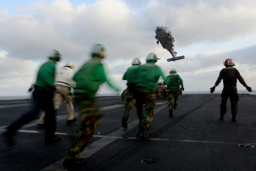 (Feb. 21, 2013) Sailors rush to retrieve pallets of cargo as an MH-60S Sea Hawk helicopter from the Eightballers of Helicopter Sea Combat Squadron (HSC) 8 finishes dropping off cargo on the flight deck of the aircraft carrier USS John C. Stennis (CVN 74) during a replenishment-at-sea.
