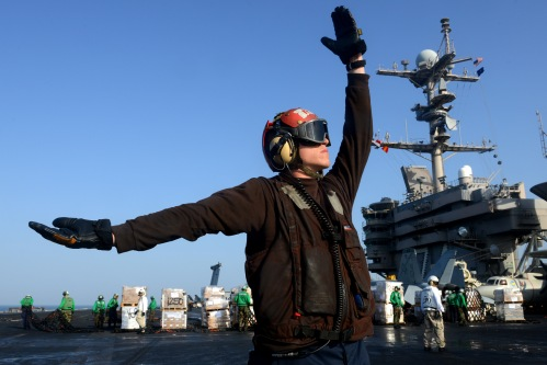 U.S. 5TH FLEET (March 9, 2013) A Sailor signals to a helicopter to drop off cargo on the flight deck aboard the aircraft carrier USS John C. Stennis (CVN 74) during a replenishment-at-sea.