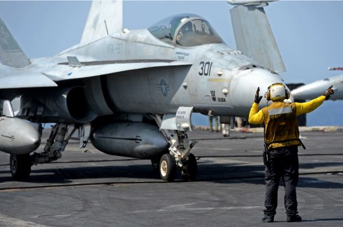 U.S. 5TH FLEET (March 11, 2013) Aviation Boatswain's Mate (Handling) 3rd Class Danangelo Tulabot, from the Philippines, directs an F/A-18C Hornet from the Warhawks of the Strike Fighter Squadron (VFA) 97 on the flight deck aboard the aircraft carrier USS John C. Stennis (CVN 74).