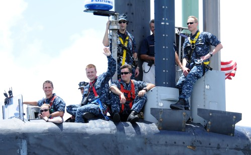POLARIS POINT, Guam (April 11, 2013) – Sailors aboard the Ohio-class guided-missile submarine USS Ohio (SSGN 726) wave from the bridge as the submarine pulls into Apra Harbor to conduct an exchange of command between their Gold and Blue crews.