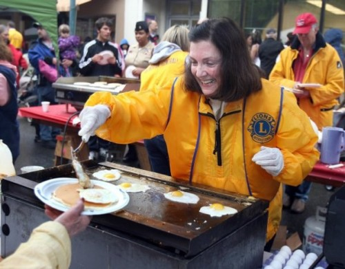 Denise Zaske from Poulsbo working with the Bremerton Central Lions serves pancakes, and eggs at the pancake breakfast before the Armed Forces Day Parade in downtown Bremerton. LARRY STEAGALL / KITSAP SUN