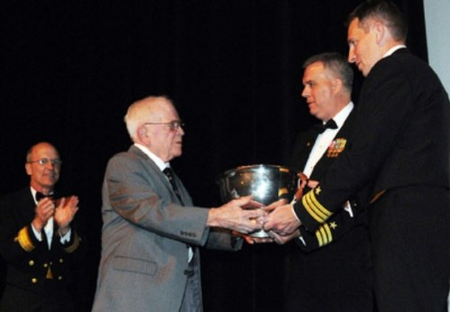 Remember the Maine | Retired Capt. Will Lent presents the Olympic Trophy to Cmdr. Mark Schmall and Cmdr. Rich Massie, commanding officers of USS Maine (SSBN 741), at the Bremerton Armed Forces Gala as Rear Adm. Bob Hennegan, commander of Submarine Group 9, looks on. The trophy is awarded annually to the top ballistic missile submarine in the Pacific Fleet.