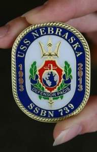 The front side of a commemorative coin minted for the 20th anniversary of the USS Nebraska depicts the submarine's crest.
