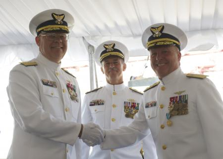Rear Adm. Richard T. Gromlich (left) and Rear Adm. Keith A. Taylor (right) shake hands after Gromlich relieved Taylor of command of the 13th Coast Guard District during a formal ceremony presided over by Vice Adm. Paul F. Zukunft (center), commander of Coast Guard Pacific Area and Defense Forces West, held at Coast Guard Base Seattle, June 28, 2013. Taylor was recognized during the ceremony for his efforts in strengthening partnerships with local, state, federal and international organizations during his two years in command.