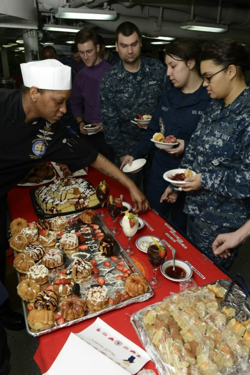 Culinary Specialist 1st class Kwaniesha Booth does a last minute check on a dessert table for a Valentines Day bake off aboard the aircraft carrier USS John C. Stennis (CVN 74).