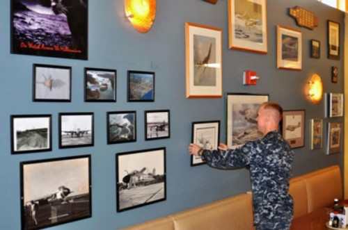 Culinary Specialist 2nd Class Sean Stephens of VAQ-131 adjusts one of many historic pictures now hanging in the Admiral Nimitz Hall as part of a recent galley décor project.