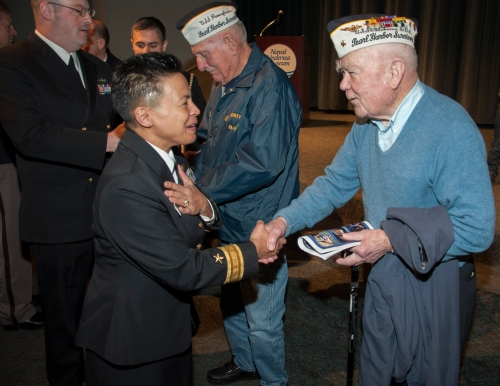 KEYPORT, Wash. (Dec. 7, 2013) Rear Adm. Bette Bolivar, left, commander of Navy Region Northwest, gives her personal coin to Pearl Harbor survivor Roy Carter during a remembrance ceremony at the Naval Undersea Warfare Center Jack Murdock Auditorium. The ceremony honored the 2,403 Americans who died during the Japanese attack at Pearl Harbor on Dec. 7, 1941.