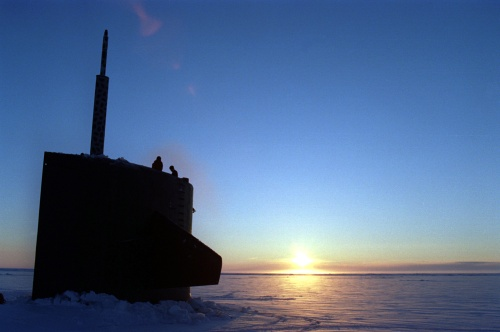 The U.S. Navys attack submarine USS Pogy (SSN 647) surfaces through the an Arctic ice flow at sunrise.