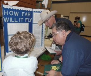 """Navy League Judges Tex Lewis (with hat) and Louis Mejia listen to third grader A. Nesnadny explain his project """"How Far Will it Fly?"""" Nesnadny was one of the Navy League Award recipients in the Grade 1-3 age group."""