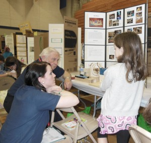 Navy League Judges Bob Lamb and Lauren Lomax listen to fourth grader M. Hillier explain her DC Motor project project. Hillier was one of the Navy League Award recipients in the Grade 4-6 age group.