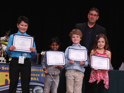 Caption: Kevin Torcolini, Board Member of the Navy League of the United States Bremerton/Olympic Peninsula Council, presents cash awards and certificates to winning students in Grades 1-6 at the 2014 Washington State Science and Engineering Fair. Winners in this age group (foreground left to right) were K. Urrutia from View Ridge Elementary School in Bremerton, WA, A. Velmurugan from Julia Butler Hansen Elementary School in Olympia, WA, A. Nesnadny from Saint Paul's Academy in Bellingham, WA, and M. Hillier from Puesta del Sol Elementary School in Bellevue, WA.