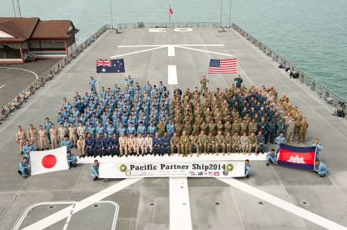 SIHANOUKVILLE, Cambodia (June 19, 2014) Australian, Japanese, and American service members pose for a photo aboard the Japan Maritime Self-Defense Force amphibious tank landing ship JS Kunisaki (LST 4003) upon arrival in Cambodia during Pacific Partnership 2014 .