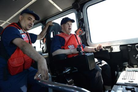 Petty Officer 2nd Class Daniel M. Caraballoa (left), a machinery technician assigned to Coast Guard Maritime Forces Protection Unit Bangor in Silverdale, Wash., explains how to operate a 64-foot Special Purpose Craft -- Screening Vessel to Christopher Marten, a Washington state resident with exceptional needs, while underway in Hood Canal, July 9, 2014.