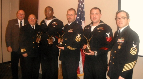 The Trident Training Facility Pacific, Bangor, WA (TTF Bangor) 2014 Sailor of the Year (SOY) and Junior SOY, along with two Instructors of the Year, were recognized by the Navy League of the United States (NLUS) Bremerton/Olympic Peninsula Council during an October 14th luncheon. Assembled left to right: NLUS Council President Larry Salter; TTF Bangor Executive Officer, CDR John Mohn Jr.; 2014 Junior SOY and 2014 Junior Instructor of the Year, MT2(SS) Charles A. McAllister; MMC(SS) Royce Glenn, 2014 Senior Instructor of the Year; 2014 SOY, MT1(SS) Alexander Pelletier; and Command Master Chief, CMDCM(SS/SW) James Willis