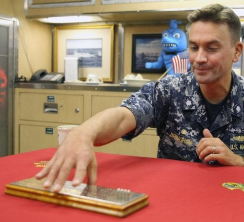 The USS Bremerton's commanding officer, Wes Bringham, and the historic cribbage board game in the ward room. LARRY STEAGALL / KITSAP SUN