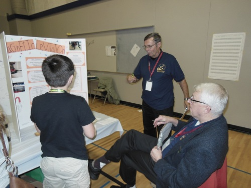 Navy League judges Don Krump (standing) and Mike Sullivan (seated) talk to a student at the 2015 Washington State Science and Engineering Fair about his project on magnetic levitation.