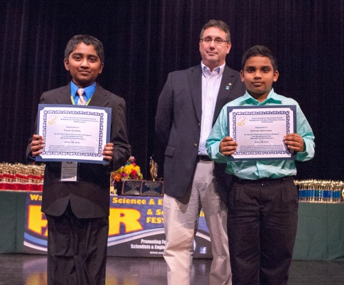 "Kevin Torcolini (center), Vice President of the Navy League of the United States Bremerton/Olympic Peninsula Council, presents cash awards and certificates to winning students in Grades 4-6 at the 2015 Washington State Science and Engineering Fair. Winners in this age group were (left) Pranav Gundrala from Jefferson Middle School in Olympia, WA for ""Fueling the Future--A Water Splitting Catalyst Efficiency Comparison,"" and Hariharan Malurugan (right)"